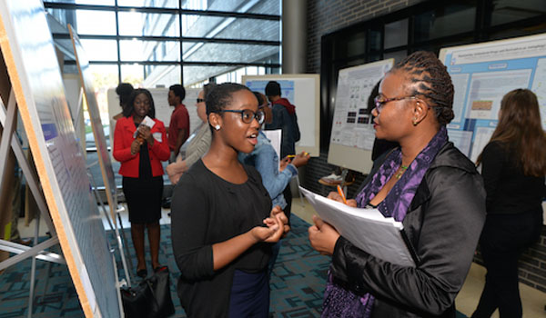 Two ladies standing at a poster presentation